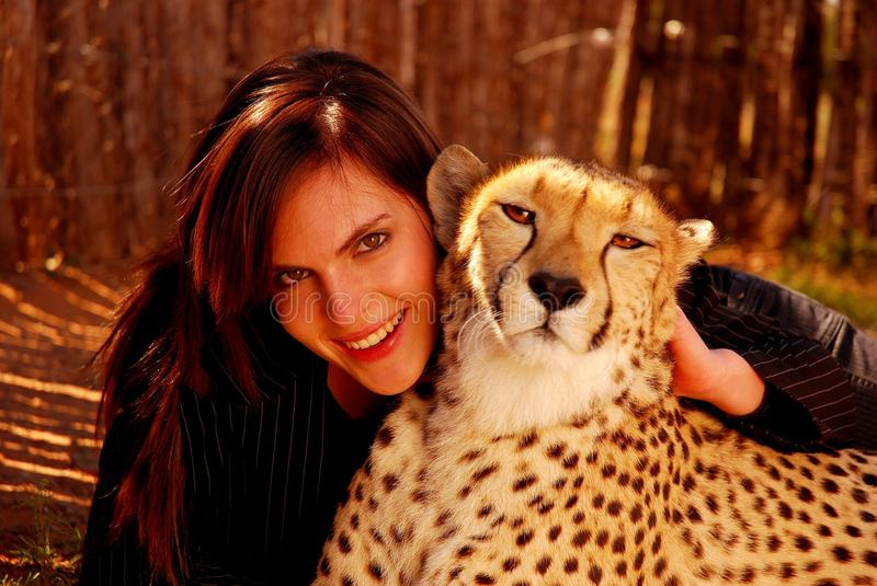 African wildlife. Outdoor portrait of an attractive caucasian young woman cuddling her beautiful tame African Cheetah pet outdoors