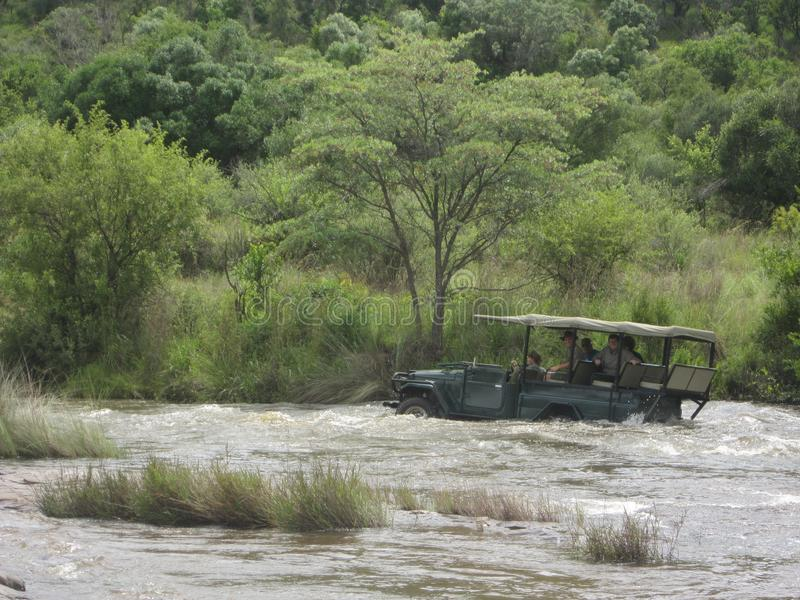 African Wildlife - Game drive - The Kruger National Park. Game drive vehicle crossing over a river in the water stock images