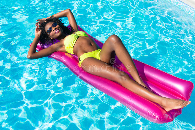 African woman on air mattress in swimming pool royalty free stock images