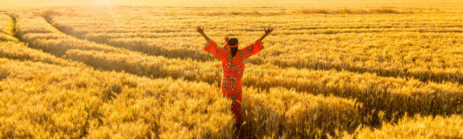 African woman arms raised in a field of crops at sunset or sunrise panorama. African woman in traditional clothes standing, arms raised, in field of barley or stock image