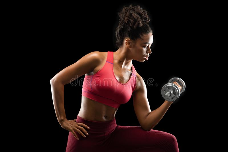 African woman bodybuilder doing single arm dumbbell curl. African woman bodybuilder doing workout with dumbbells, single arm db curl, side view, black studio royalty free stock image