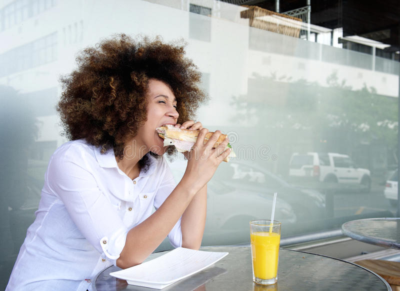African woman in cafe eating sandwich royalty free stock photos