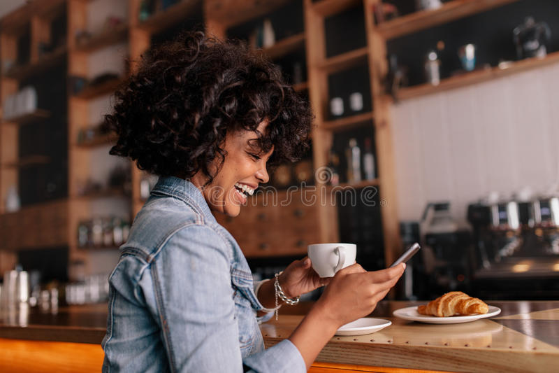 African woman cafe using mobile phone and smiling royalty free stock photography