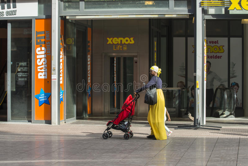 An African woman carrying a baby carriage stock photo