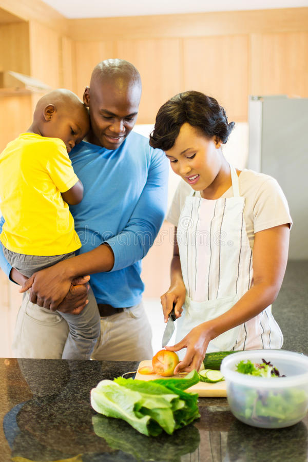 African woman chopping vegetables. African women chopping vegetables with husband and kid in the kitchen royalty free stock image