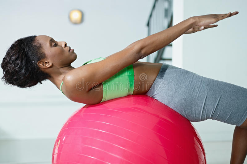 African woman doing series of sit-ups in gym royalty free stock photo