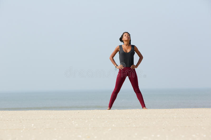 African woman doing yoga breathing exercise stock photo