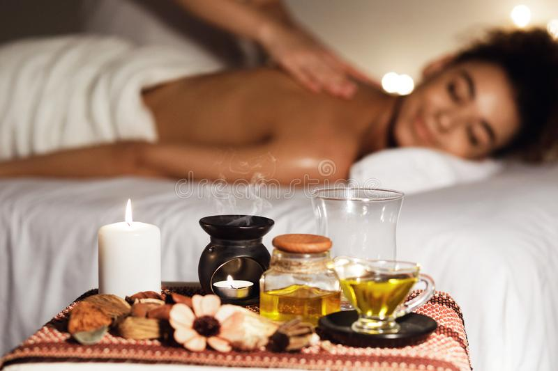 African woman enjoying aromatherapy massage in luxury spa. With candles on foreground stock photos