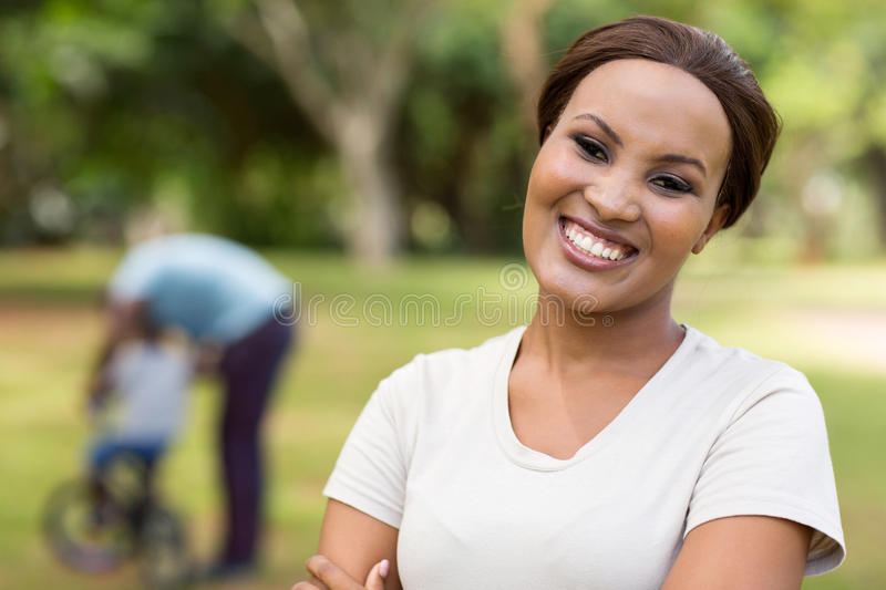 African woman family. Beautiful african woman standing in front of family outdoors royalty free stock image