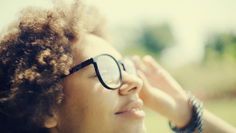 African woman feeling the sun shine on her face stock photos