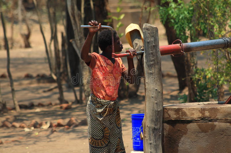 African woman fetching water royalty free stock photo