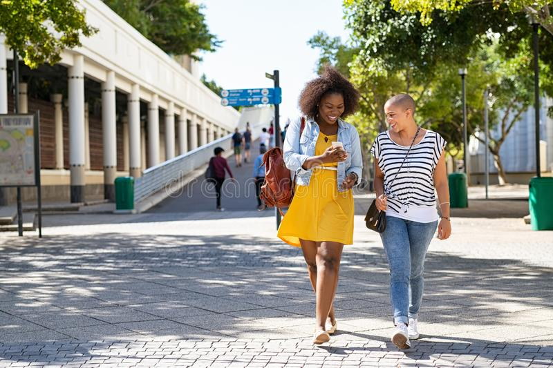 African woman with friend using phone royalty free stock photo