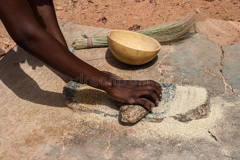 An African Woman Grinding Cereals Millet Into Flour Using Traditional Grindstones Burkina Faso