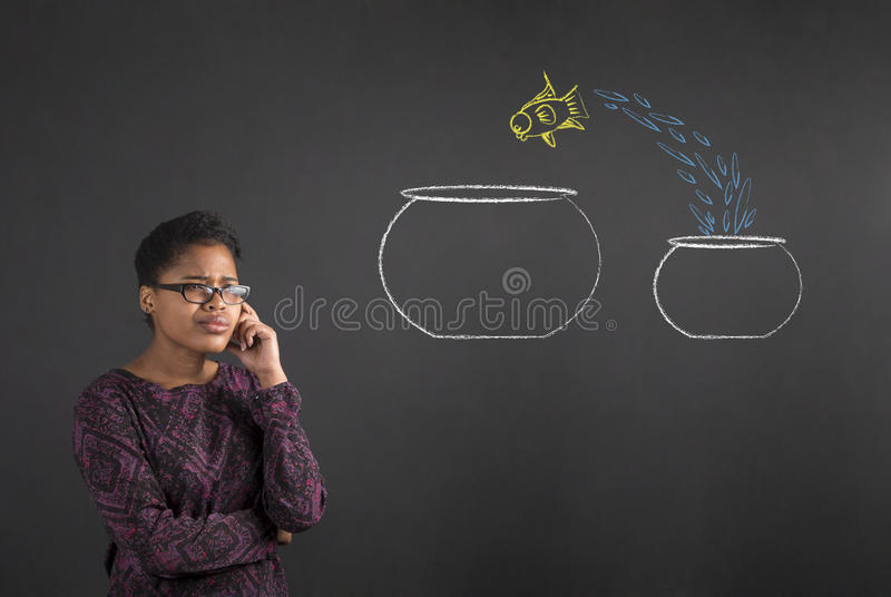 African woman with hand on chin thinking jumping fish on blackboard background royalty free stock photography