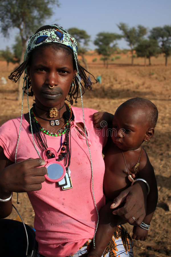 African woman with her baby. Typical peulh woman of Mali Peul can be considered the largest nomadic group in the world. Called the British and Fulani Fellah stock images