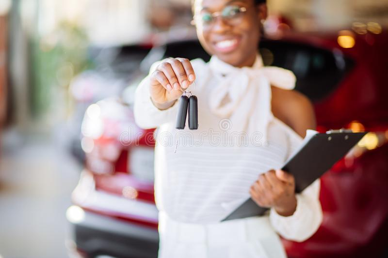 African woman with her new car showing key royalty free stock images