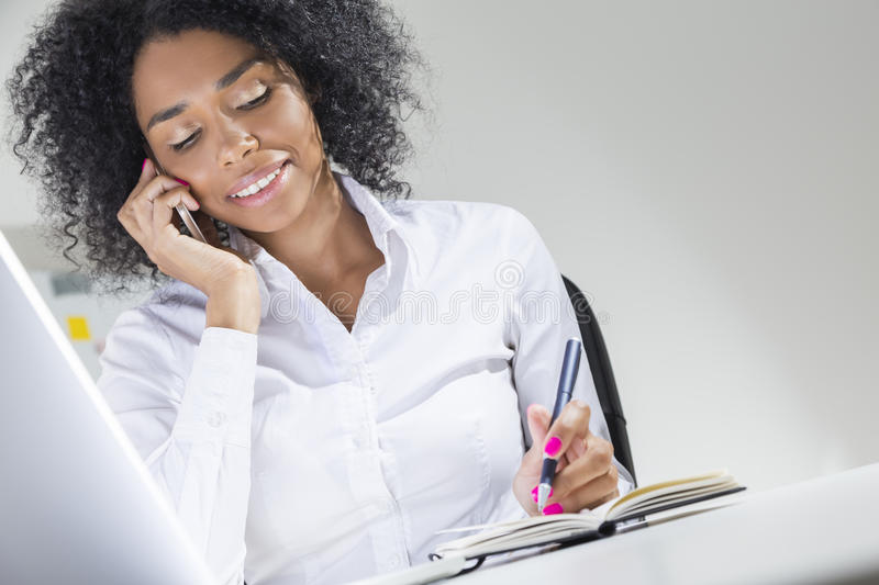 African woman on her phone in the office with laptop stock photos