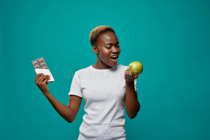 African woman holding apple and dark chocolate bar. royalty free stock photo