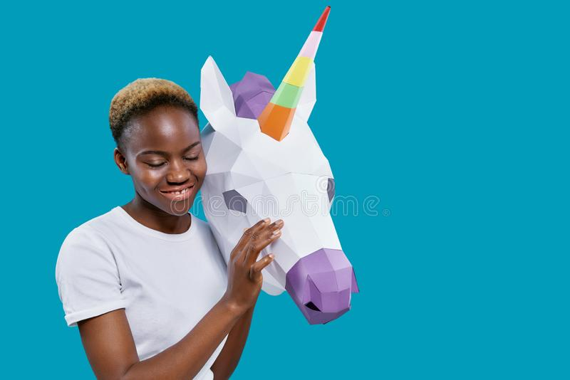 African woman holding 3D paper unicorn head. Cheerful african woman holding paper unicorn head on blue background with copy space. Positive girl in white t royalty free illustration