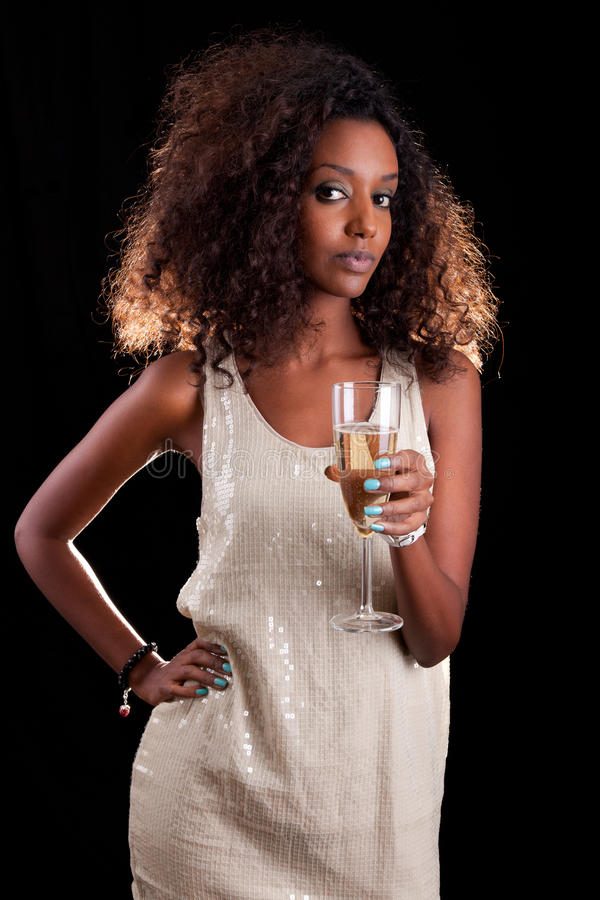 African woman holding a glass of champagne royalty free stock image