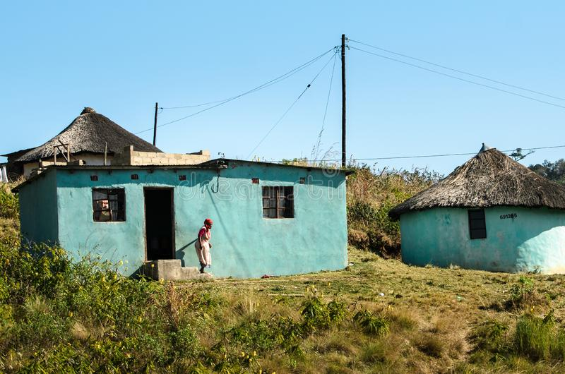 African woman out of her traditional mud house in South Africa. Apartheid, zululand KwaZulu-Natal. African woman out of her traditional mud house in a small stock photos