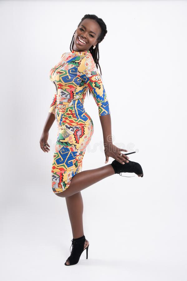 African woman portrait studio shot. Beautiful African woman hair dreadlocks with a happy posture wearing a flower-patterned dress, wearing black high-heeled stock photos