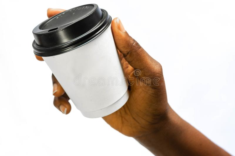 African Woman`s hands holding white paper coffee cup or another hot drink in the cold season on white. Creative Mockup of royalty free stock images