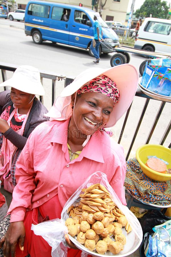 An african woman selling samosas at a market in Accra, Ghana. Happy laughing with local taxis called tro tro stock image