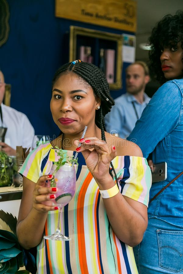 African woman sipping a cocktail and generally enjoying a day out at a Food and Wine Fair. Johannesburg, South Africa - October 14 2017: African woman sipping a stock image