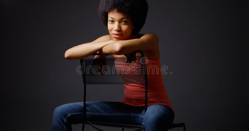 African woman sitting casually with arms over back of chair. Portrait African woman sitting casually with arms over back of chair stock photography