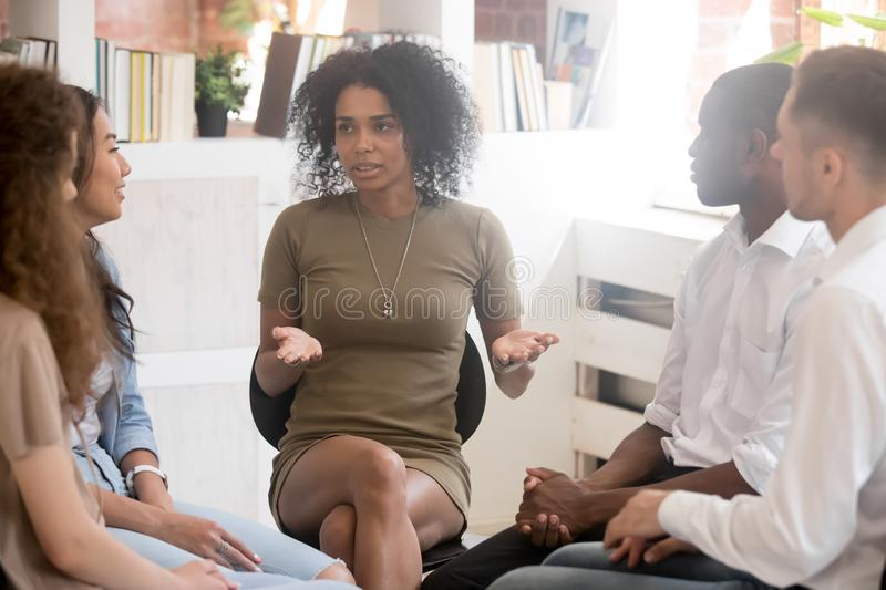 African woman speaking at diverse team training or group therapy. African women psychologist coach speaking at diverse team training or group therapy session royalty free stock photography