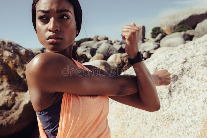 African woman stretching arms at the beach stock photo