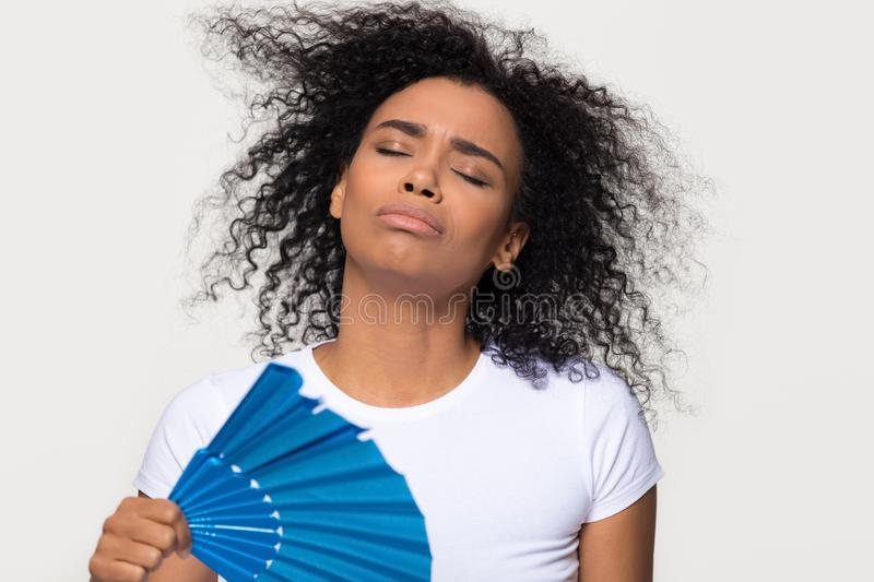 African woman sweating from heat waving fan isolated on background. African woman sweating feeling uncomfortable from heat stroke in hot summer weather holding stock photo