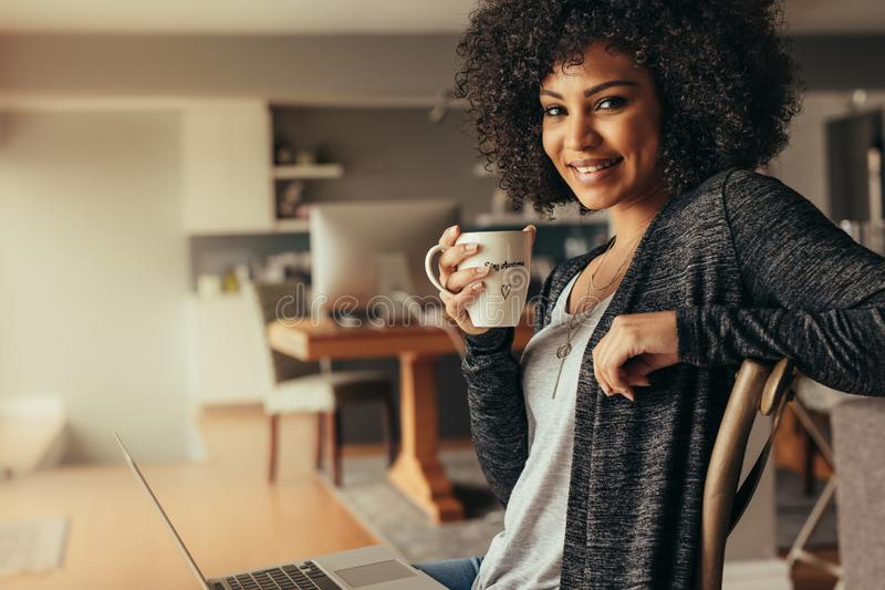 African woman taking coffee break while working from home royalty free stock image