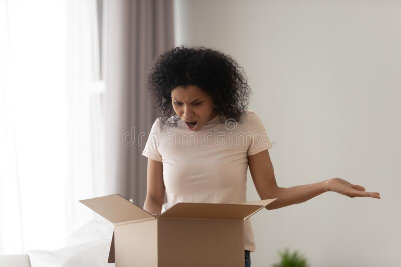 African woman unpacking parcel feels angry see damaged ordered goods royalty free stock images