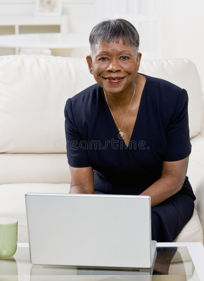 African woman using laptop on sofa at home