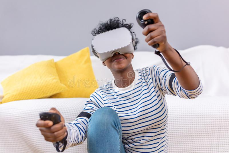 African woman watching video using VR glasses with remote control at home. royalty free stock photo