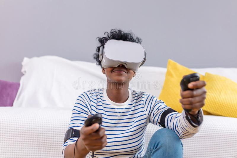 African woman watching video using VR glasses with remote control at home. royalty free stock photography