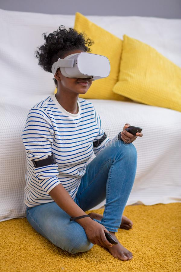 African woman watching video using VR glasses with remote control at home. stock images