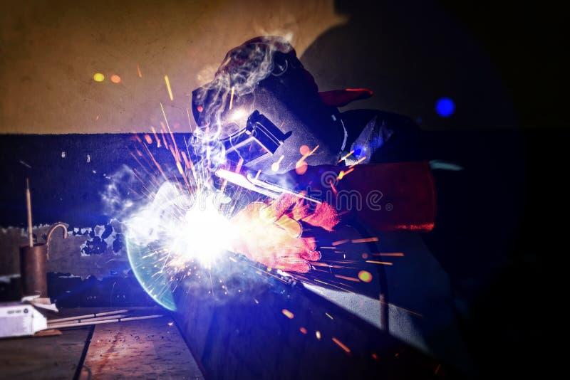 African worker. Motswana welder worker in a Botswana workshop, welding two pieces of metal royalty free stock image