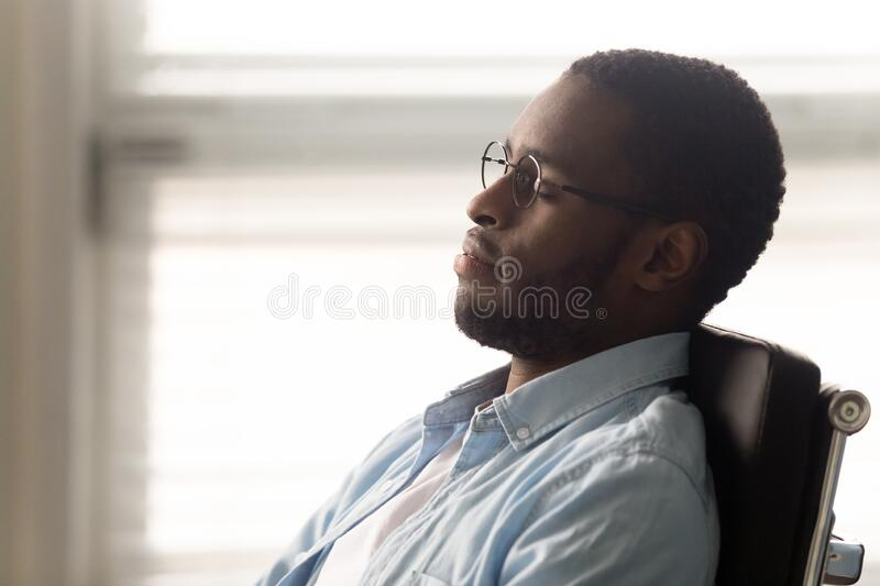 African worker resting seated on ergonomic office chair at workplace. Close up African office worker closed eyes resting enjoy break dreaming about future career royalty free stock image