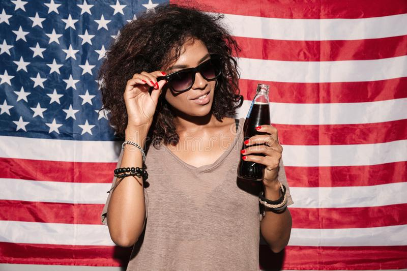 African young lady drinking aerated water. Looking aside. Image of serious african young lady wearing sunglasses standing over USA flag drinking aerated water stock photography