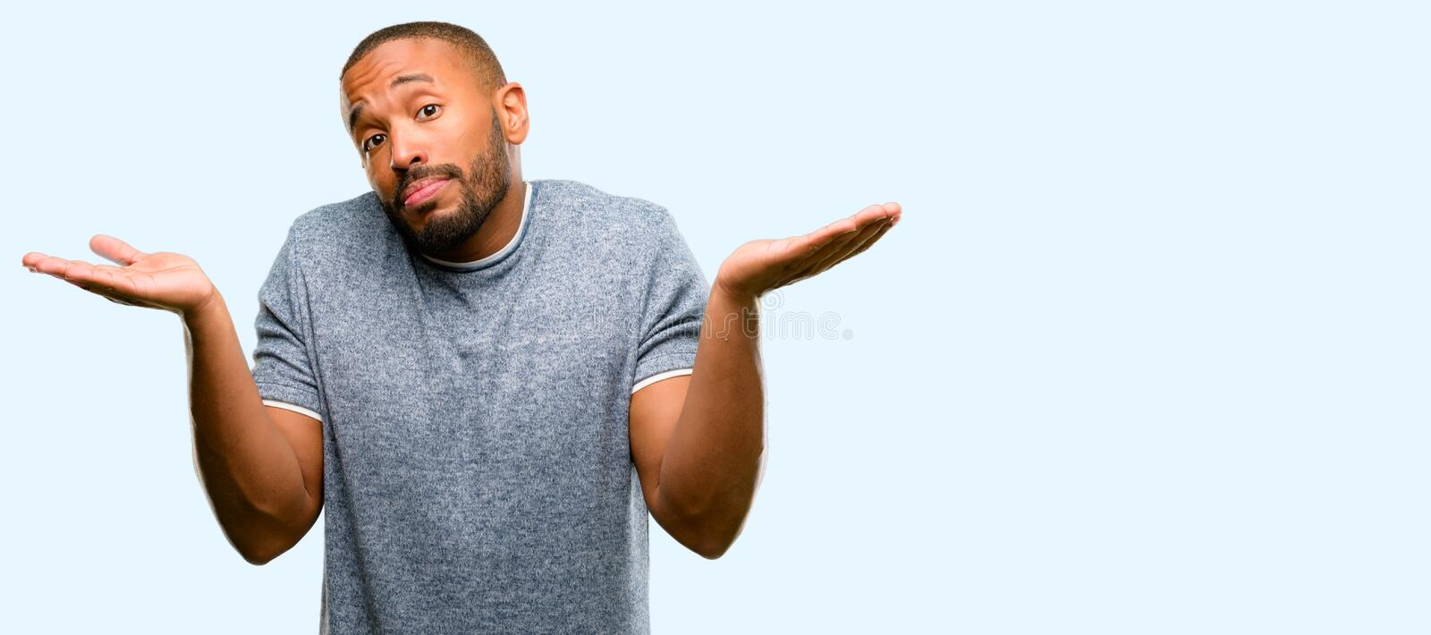 African young man over white background. African american man with beard doubt expression, confuse and wonder concept, uncertain future shrugging shoulders over royalty free stock images