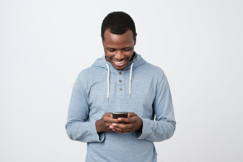 African young man using mobile phone chatting in internet with her friends. royalty free stock photo