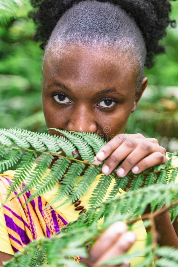African woman hid behind green leaves in jungle stock image