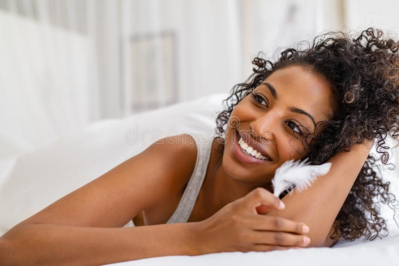 African young woman holding feather on bed stock image