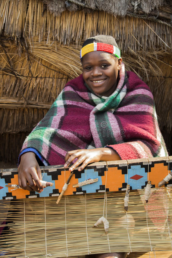 African Zulu woman weaves straw carpet. South Africa, Gauteng, Lesedi Cultural Village (unique center of African culture) - 04 July, 2015. Smiling beautiful royalty free stock photo