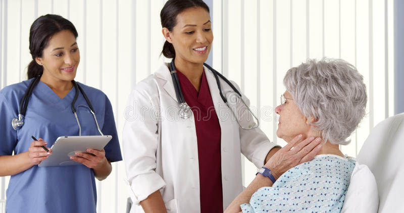 AfricanAmerican doctor talking to elderly woman patient with nurse. African American doctor talking to elderly women patient with nurse stock photography
