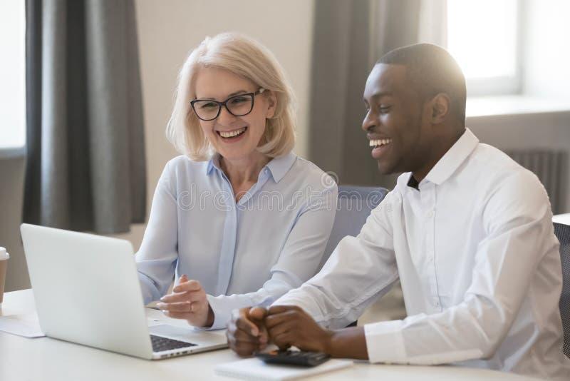 Africano feliz y colegas caucásicos que hablan en oficina en el ordenador portátil foto de archivo