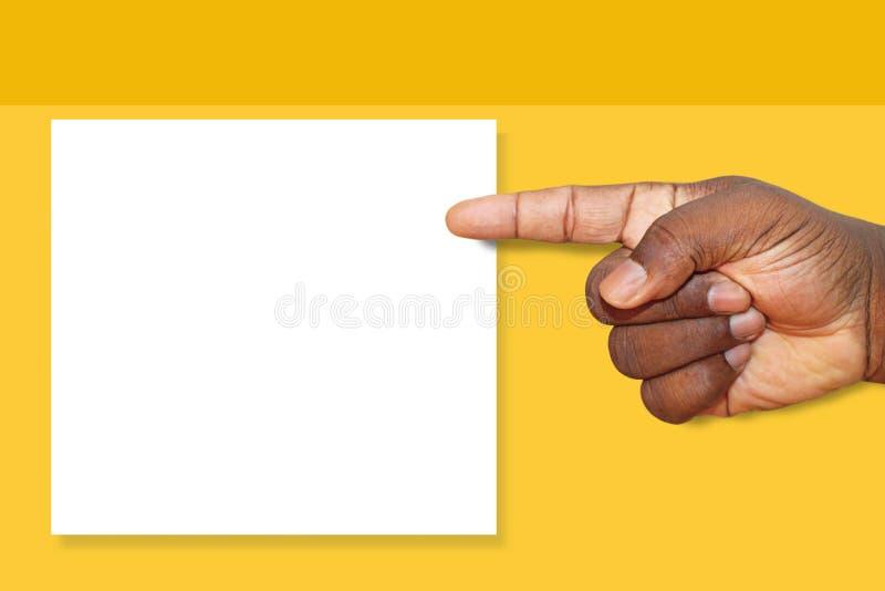 Africano, la mano dell'uomo di colore indicante ad un segno in bianco su un fondo di giallo della senape fotografia stock